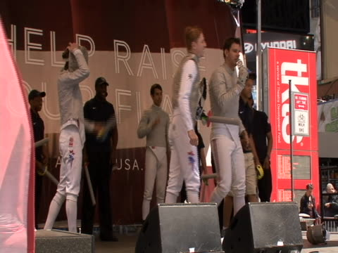 of fencing with fake swords on stage at countdown to olympics event in times square in new york city. - sport stock videos & royalty-free footage