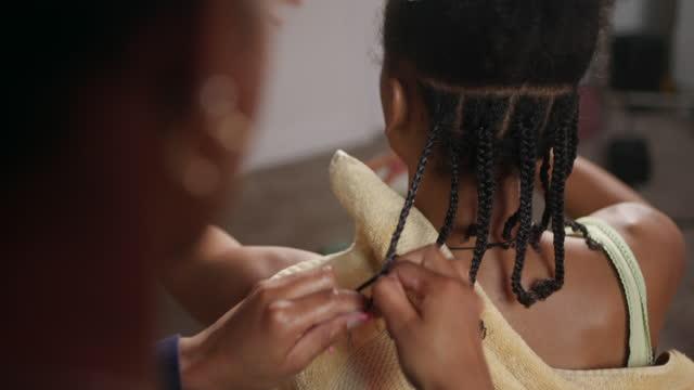 mcu of focused sister braiding her playful sister's hair - braided hair stock videos & royalty-free footage