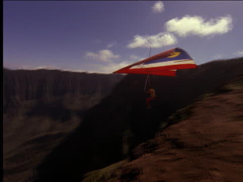 AERIAL of hang glider over rocky coastline