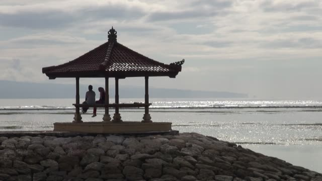 mws of indonesian tourist couple sitting in a bale on sanur beach bali in the morning with waves breaking on reef in background - pavilion stock videos & royalty-free footage