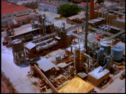 AERIAL of industrial complex with storage tanks + pipes (aluminum factory) / Brazil