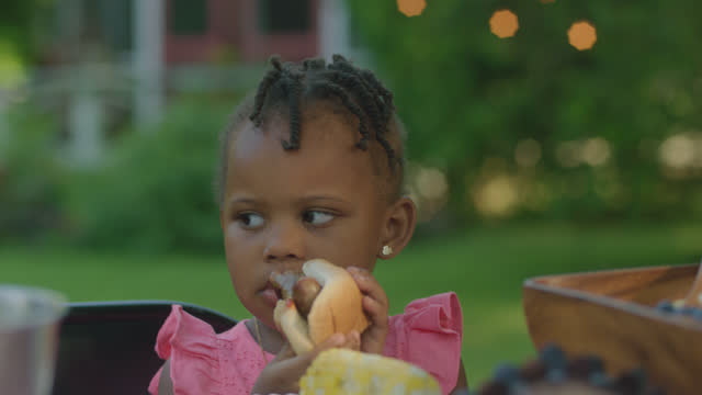 MCU of little girl eating at a table outside