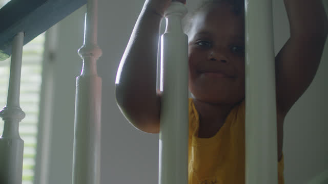 MCU of little girl playing on the stairs