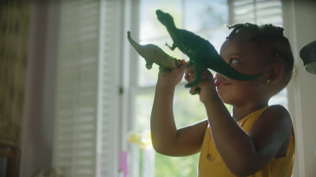 MCU of little girl playing with dinosaur toys