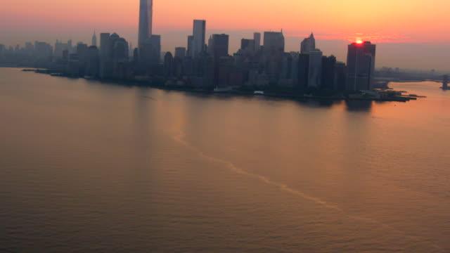 WIDE AERIAL TILT UP of Lower Manhattan skyline at sunrise