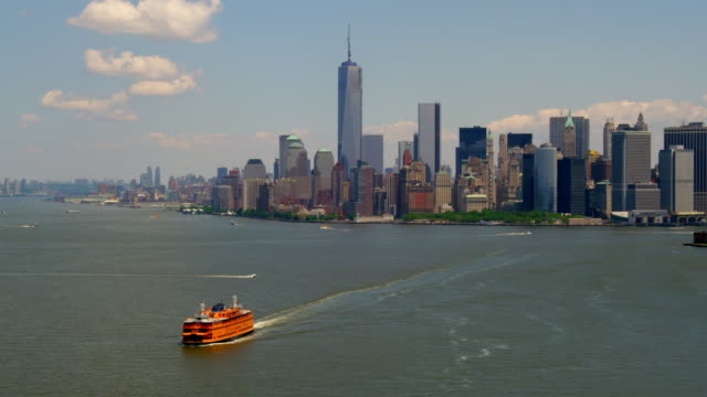 LONG AERIAL of Lower Manhattan skyline with TILT DOWN to Staten Island Ferry in New York Harbor