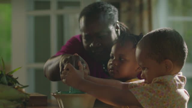 MCU of mature woman helping a little boy squeeze a lemon