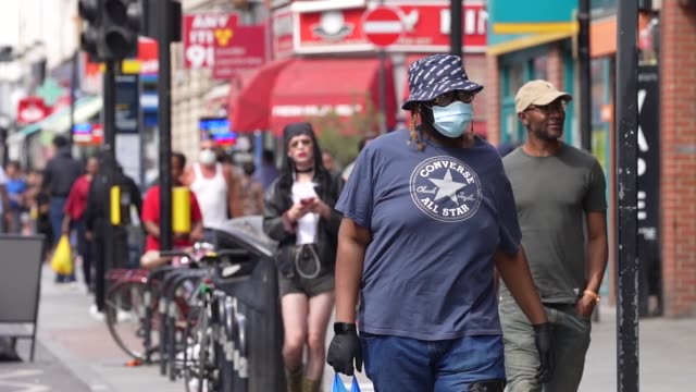 of members of the public wearing ppe face mask in dalston east london during the coronavirus covid-19 pandemic. the british government further... - black ethnicity stock videos & royalty-free footage