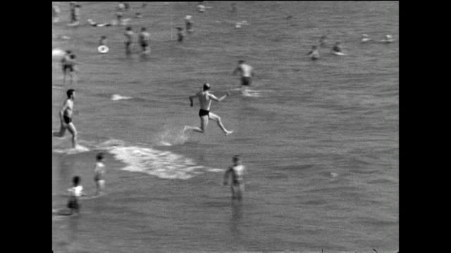 b&w has of men running into sea and falling over in water; 1963 - swimwear stock videos & royalty-free footage