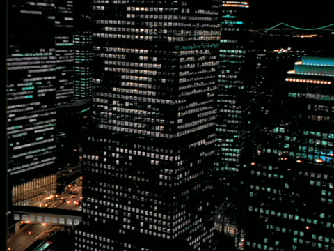 AERIAL of mirrored buildings + Woolworth Bldg at night/NYC