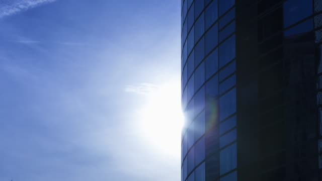 tl of moving clouds and appearing sun on office building in financial district - curtain wall facade stock videos and b-roll footage