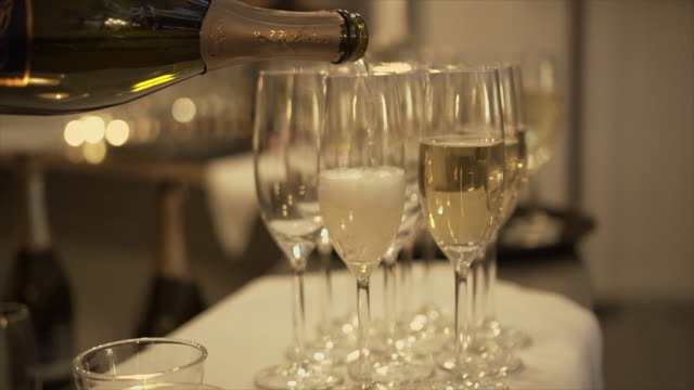 slow motion of pouring champagne glasses on table. - aperitivo video stock e b–roll