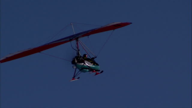 of powered hang glider w/ unidentifiable male operating in pusher flying in clear blue sky flight cruise glide gliding soaring eyes in the sky - hang gliding stock videos and b-roll footage