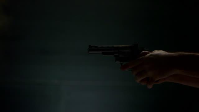 cu side view of revolver shooting - pistolenschießen stock-videos und b-roll-filmmaterial