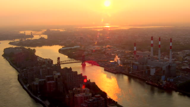 LONG AERIAL of Roosevelt Island, TransCanada Ravenswood Power Plant in Queens, and 59th Street Bridge over East River at sunrise