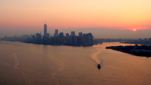 long aerial of ship in new york harbor and lower manhattan skyline in distance at sunrise - new york harbor stock videos & royalty-free footage