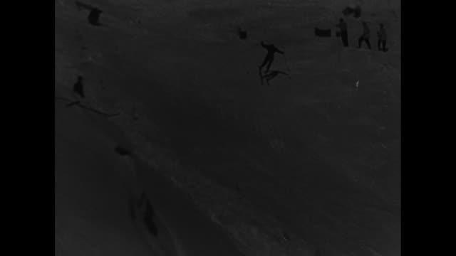 vs aerials of ski slope at st moritz w flags flying / vs contestants skiing downhill / cu low angle of spectator looking thru binoculars / cu side... - slalom skiing stock videos & royalty-free footage