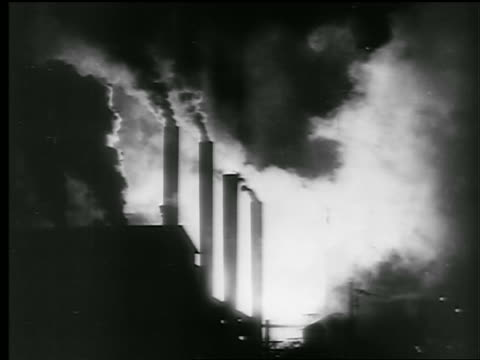 B/W 1942/43 SILHOUETTE of smokestacks of factory pouring out smoke / newsreel