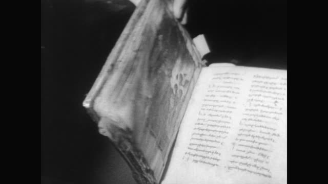 EXT of Sotheby's auction house / worker carefully handles 700 year old Armenian gospel manuscripts the sale of which was cancelled due to protests...