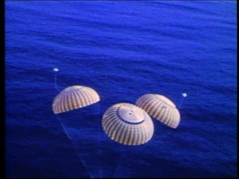 aerial of space capsule with parachutes splashing down / apollo 17 - splashdown stock videos and b-roll footage