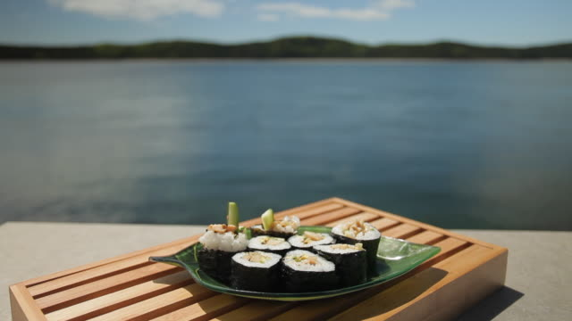 dolly shot of sushi in front of river - food styling stock videos & royalty-free footage