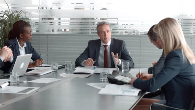 ceo of the company talking in a meeting with executives in the conference room - top capo di vestiario video stock e b–roll