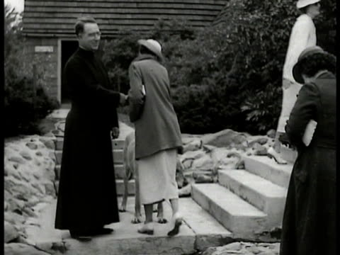 shrine of the little flower church father coughlin shaking hands w/ parishoners cu father coughlin people in aditorium cheering waving small flags - 1935 stock-videos und b-roll-filmmaterial