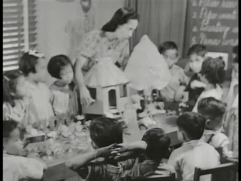 commonwealth of the philippines public school female teacher w/ nipa hut model on table surrounded by filipino kindergarten or first grade students... - philippines stock videos & royalty-free footage