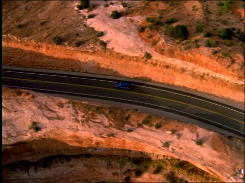 aerial of truck driving on desert road / southwest us - südwestliche bundesstaaten der usa stock-videos und b-roll-filmmaterial
