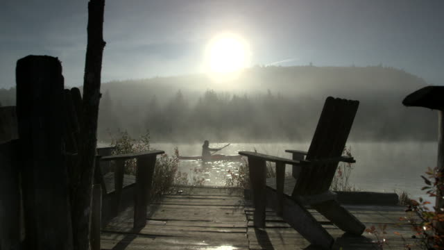 dolly shot of two chairs in front of lake on foggy day - resting stock videos & royalty-free footage