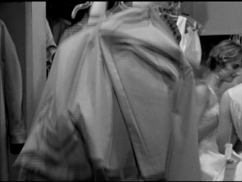 back of two unidentifiable female models in dressing room taking off dresses revealing undergarments dresses hanging on rack bg clothing designer... - 収納ラック点の映像素材/bロール