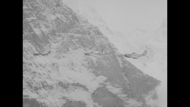 / vs of views of three airplanes with cross roundels painted on their tails flying among towering snowcovered mountains / note exact year not known... - unvollständig stock-videos und b-roll-filmmaterial