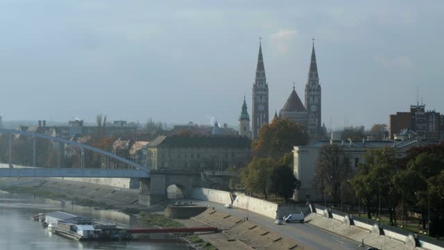 4k tl of votive church and cathedral of our lady of hungary, river tisa and szeged bridge - セゲド点の映像素材/bロール