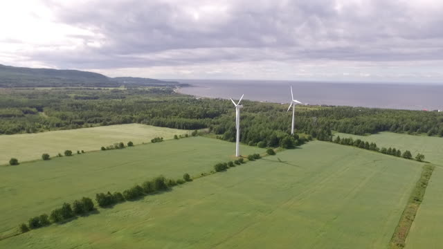 AERIAL VIEW of windmills, river and fields on windless day