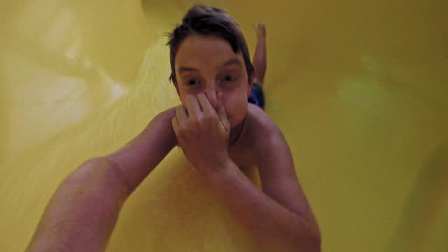 stockvideo's en b-roll-footage met selfie of young boy on vacation sliding backwards down waterslide in indoor resort while holding his nose - waterpark
