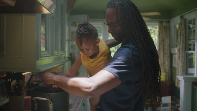 MCU of young man and child stirring a pot in the kitchen