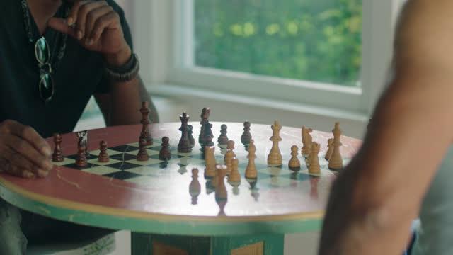 MCU of young man enjoying a game of chess