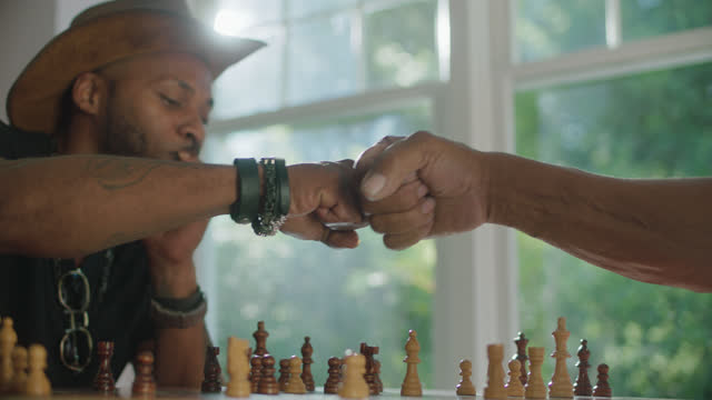 MCU of young man fist bumping his opponent in a game of chess