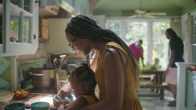MCU of young woman and child preparing food
