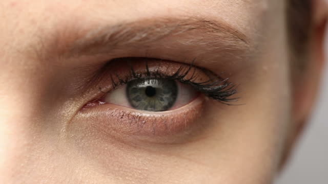 slo mo xcu of young woman's green eye as she blinks. - green eyes stock videos and b-roll footage
