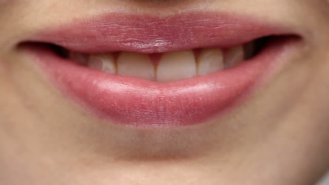 XCU of young woman's lips as she smiles and blows a kiss.