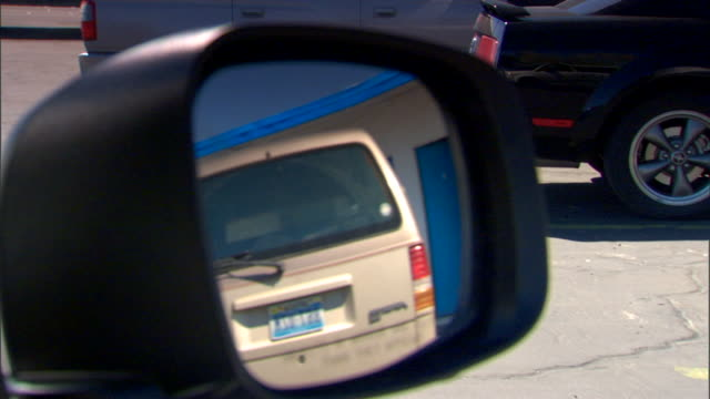 reflection off passenger side mirror while driving down unidentifiable motel rooms cars in parking lot artistic glass mirror reflect - blue glass stock videos and b-roll footage