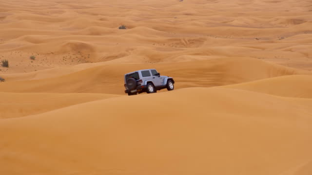 slo mo off road car driving over a sand dune - 4x4 stock videos and b-roll footage