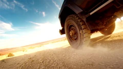 vídeos y material grabado en eventos de stock de la salida de la carretera en desierto de áfrica.   rodadura en la rueda en primer plano. - carretera de tierra