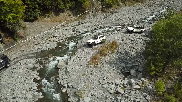 off road vehicles crossing wild mountain river. aerial view of suv cars - off road racing stock videos & royalty-free footage