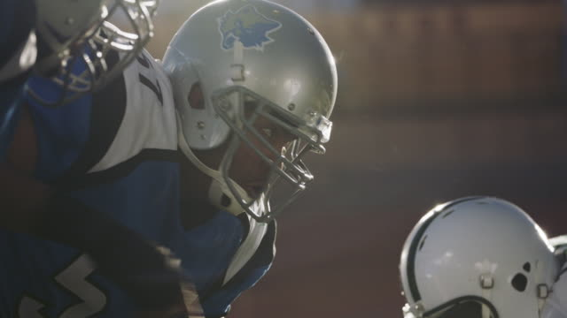 cu slo mo. offensive linemen point out players to watch across line of scrimmage in professional football game. - アメフトのユニフォーム点の映像素材/bロール