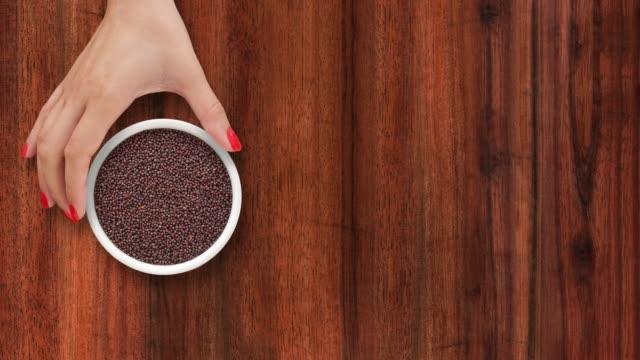 offering black mustard seeds - sfondo marrone video stock e b–roll