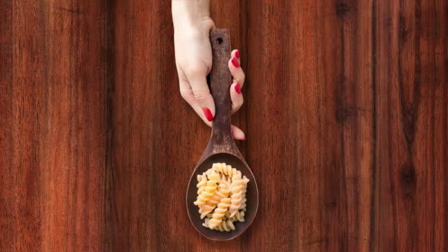 offering boiled fusilli pasta - sfondo marrone video stock e b–roll