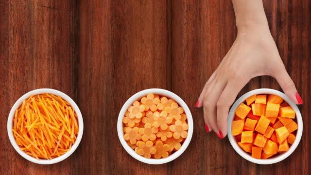 vidéos et rushes de offrant des bols avec des coupes de carotte - carotte