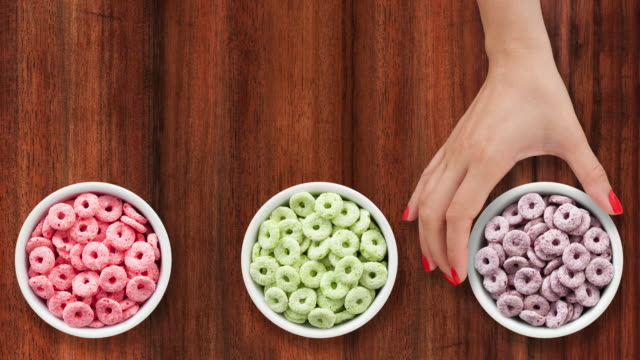 offering bowls with multicolored breakfast cereal rings - sfondo marrone video stock e b–roll